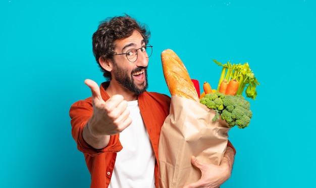 Jonge, bebaarde man die zich trots, zorgeloos, zelfverzekerd en gelukkig voelt, positief glimlacht met duimen omhoog en een zak met groenten vasthoudt