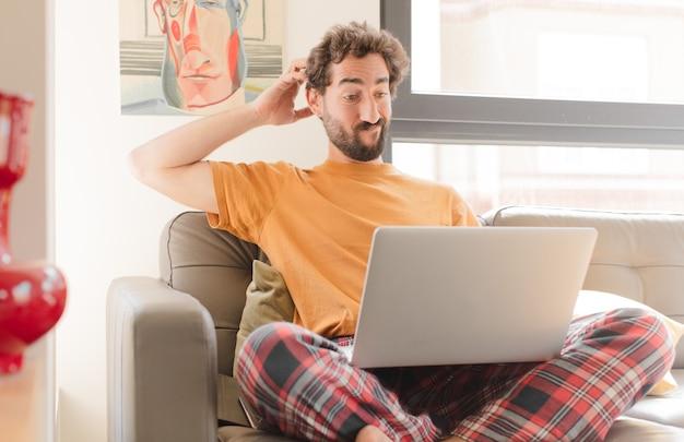 Jonge, bebaarde man die zich verbaasd en verward voelt, zijn hoofd krabt en naar de zijkant kijkt en met een laptop zit