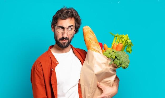 Jonge, bebaarde man die zich verdrietig, boos of boos voelt en opzij kijkt met een negatieve houding, met een zak met groenten