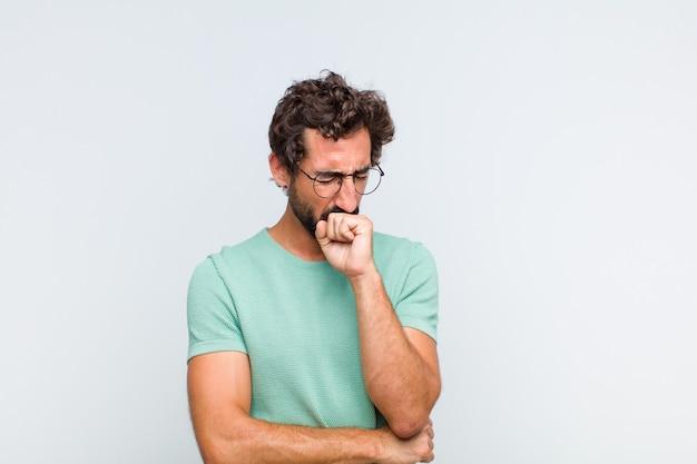 Jonge, bebaarde man die zich ziek voelt met keelpijn en griepsymptomen, hoesten met bedekte mond