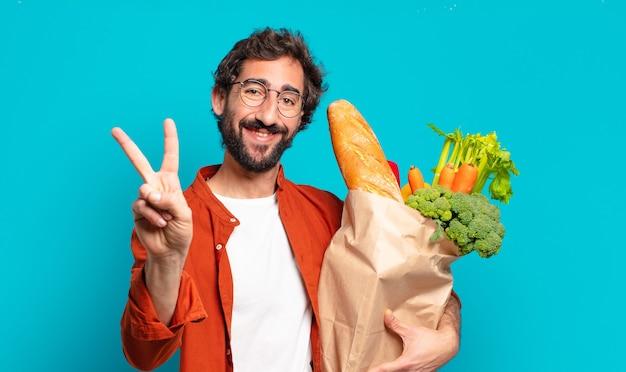 Jonge, bebaarde man glimlacht en kijkt gelukkig, zorgeloos en positief, gebaart overwinning of vrede met één hand en houdt een zak met groenten vast