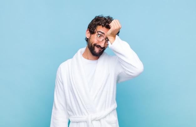 Jonge, bebaarde man in badjas met handpalm naar voorhoofd denkend oeps, na het maken van een domme fout of het zich herinneren, zich dom voelen