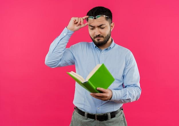 Jonge, bebaarde man in blauw shirt kijken naar boek in zijn handen bril afzetten