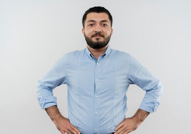 Jonge, bebaarde man in blauw shirt kijken naar voorzijde met armen op heup glimlachend zelfverzekerd staande over witte muur