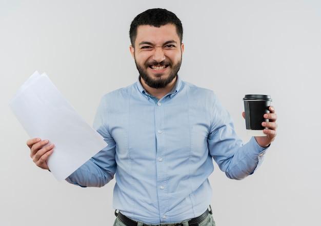 Jonge, bebaarde man in blauw shirt met koffiekopje en documenten blij en opgewonden staande over witte muur