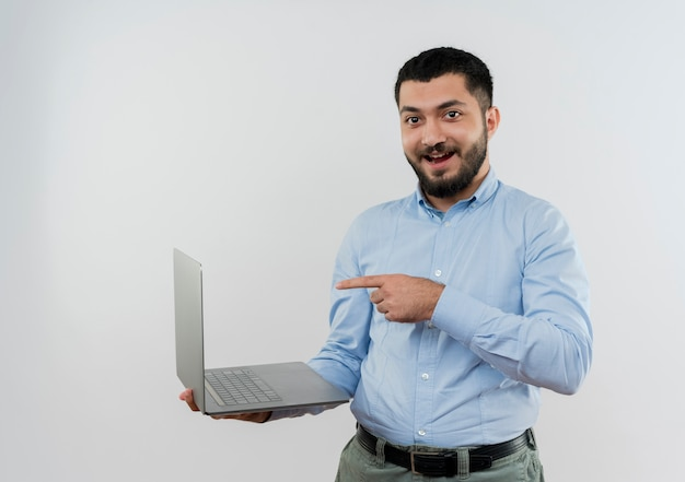 Jonge, bebaarde man in blauw shirt met laptop wijzend met wijsvinger naar het glimlachend blij en positief staande over witte muur
