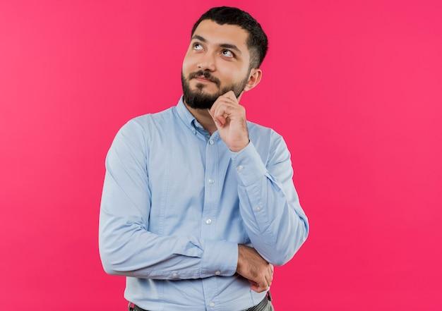 Jonge, bebaarde man in blauw shirt opzoeken met hand op kin denken
