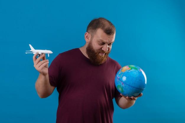Jonge, bebaarde man in bruin t-shirt met globe en speelgoed vliegtuig globe kijken met sceptische uitdrukking