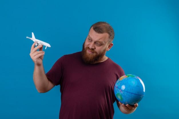 Jonge, bebaarde man in bruin t-shirt met globe en speelgoed vliegtuig speelgoed kijken met sceptische uitdrukking op gezicht
