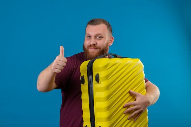 Jonge, bebaarde man in bruin t-shirt met reiskoffer kijken camera glimlachen duimen opdagen