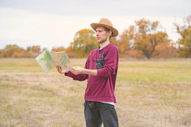 Jonge, bebaarde man in de zomerhoed verdwaald in het bos en zoek de weg op de kaart