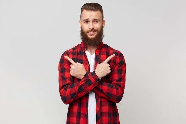 Jonge, bebaarde man in geruit overhemd met mode kapsel met gekruiste armen toont de wijsvingers rechts en links, twijfels weet niet wat te kiezen, moeilijk om een beslissing te nemen, op witte achtergrond