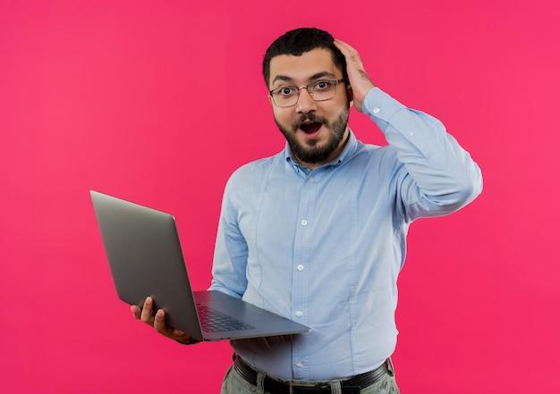 Jonge, bebaarde man in glazen en blauw shirt met laptop wordt verrast en verward