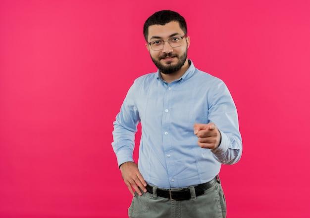 Jonge, bebaarde man in glazen en blauw shirt wijzend met de vinger op camera smilng met blij gezicht