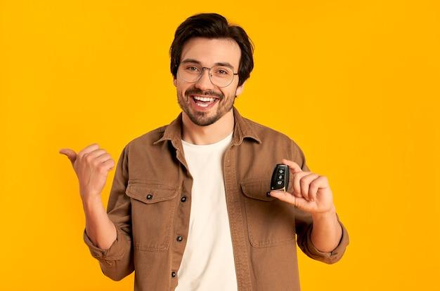 Jonge, bebaarde man in glazen houdt sleutels afstandsbediening van een nieuwe auto geïsoleerd. aankoop, autoverhuur.