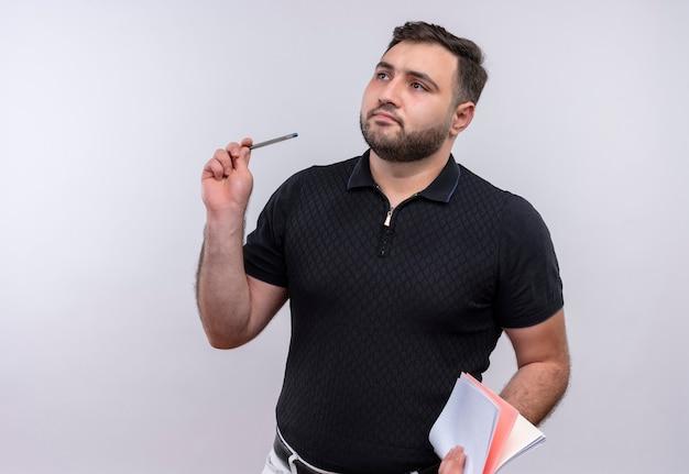 Jonge, bebaarde man in het zwarte notitieboekje en de pen van de overhemdholding die opzij met pencive uitdrukking kijken