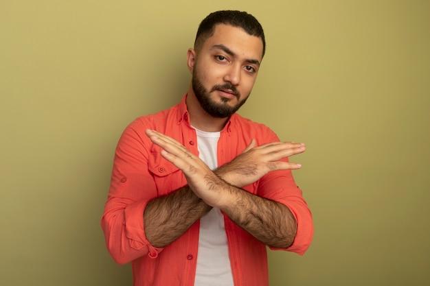 Jonge, bebaarde man in oranje overhemd stop gebaar kruising handen met ernstig gezicht staande over lichte muur maken