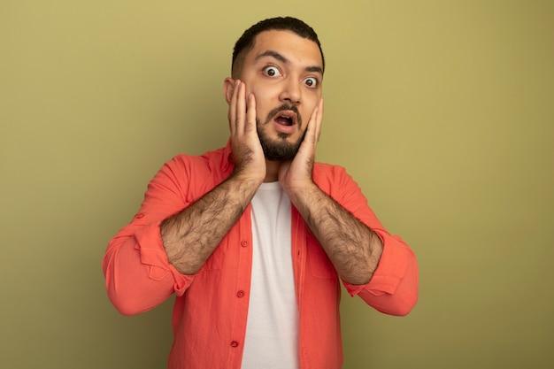 Jonge, bebaarde man in oranje overhemd verbaasd en verrast staande over lichte muur
