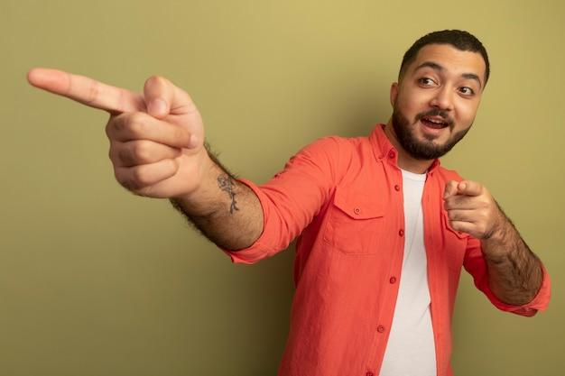 Jonge, bebaarde man in oranje overhemd wijzend met wijsvingers naar iets blij en positief glimlachend vrolijk staande over lichte muur