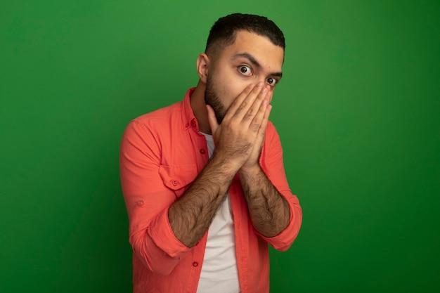 Jonge, bebaarde man in oranje overhemd wordt geschokt die mond bedekken met handen die zich over groene muur bevinden