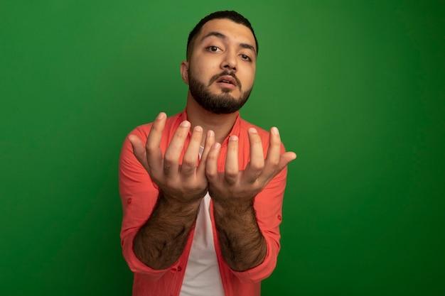 Jonge, bebaarde man in oranje shirt met armen voor hem bedelen staande over groene muur