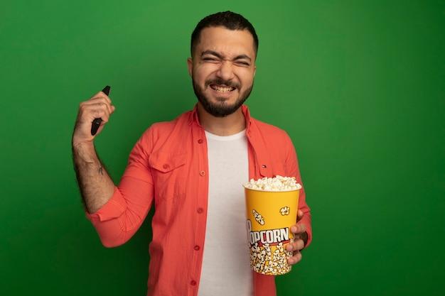Jonge, bebaarde man in oranje shirt met emmer met popcorn en tv afstandsbediening blij en opgewonden hand opsteken staande over groene muur