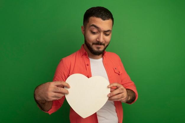 Jonge, bebaarde man in oranje shirt met kartonnen hart te kijken met een glimlach op gezicht staande over groene muur
