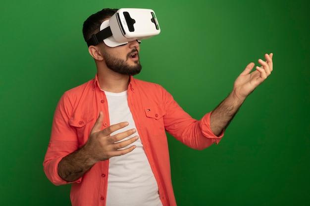 Jonge, bebaarde man in oranje shirt met virtual reality-bril gebaren met handen permanent over groene muur