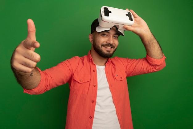 Jonge, bebaarde man in oranje shirt met virtual reality-bril op zijn hoofd op zoek wijzend met wijsvinger blij en positief glimlachend staande over groene muur