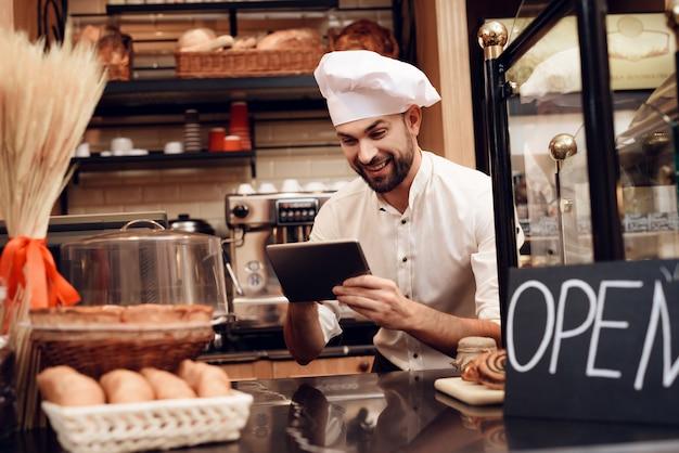 Jonge, bebaarde man in schort staande in bakkerij