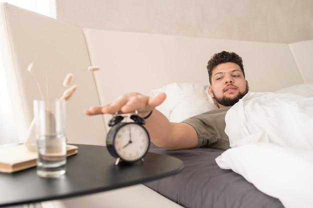 Jonge, bebaarde man in t-shirt die op de wekkerknop drukt terwijl hij onder een witte deken in een groot bed ligt na het slapen in de ochtend