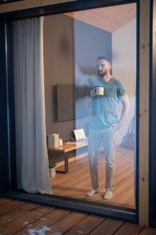 Jonge, bebaarde man in vrijetijdskleding die een mok met warme drank vasthoudt en door een groot raam kijkt terwijl hij op een houten vloer in de woonkamer staat