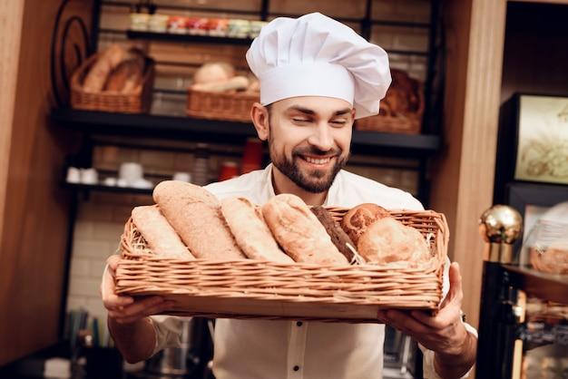 Jonge, bebaarde man in witte dop staat in de bakkerij.