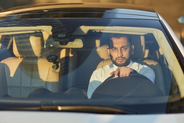 Jonge, bebaarde man in zijn auto zit en camera te kijken tijdens het rijden
