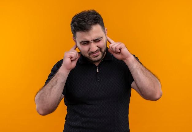 Jonge, bebaarde man in zwart overhemd oren met vingers sluiten met geïrriteerde uitdrukking