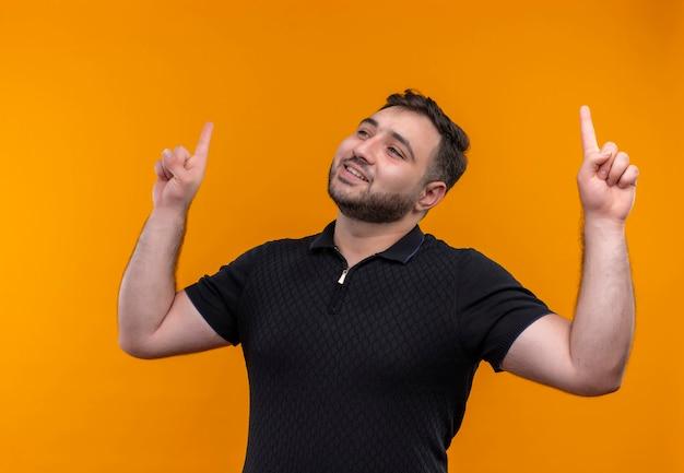 Jonge, bebaarde man in zwart shirt blij en positief opzoeken en met wijsvingers omhoog wijzen