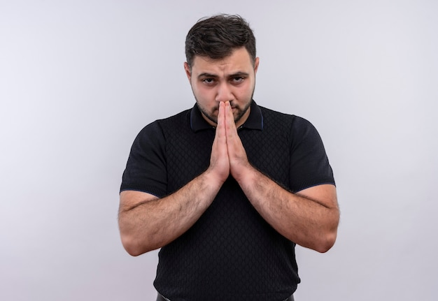 Jonge, bebaarde man in zwart shirt hand in hand zoals bidden bezorgd en emotioneel op zoek
