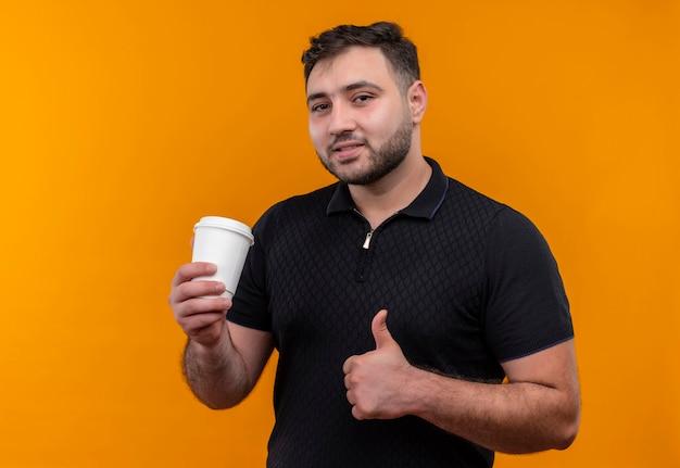 Jonge, bebaarde man in zwart shirt holdng koffiekopje duimen opdagen glimlachen