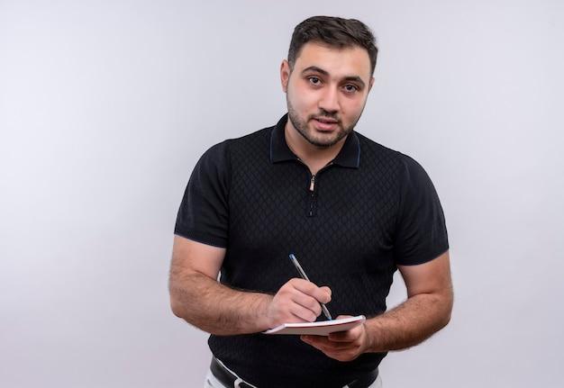 Jonge, bebaarde man in zwart shirt kijken naar camera schrijven iets in notitieblok