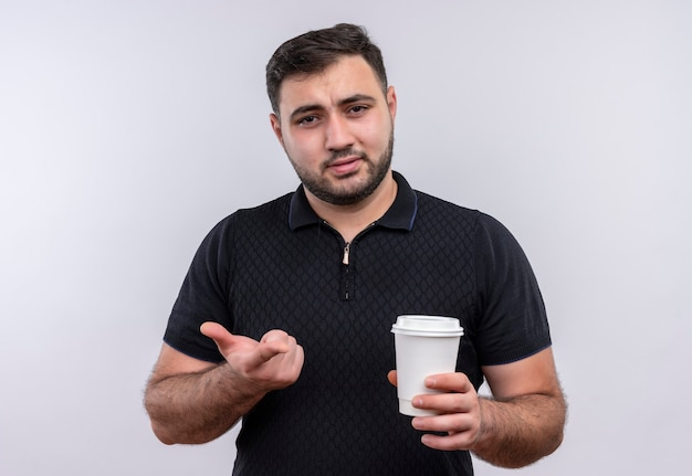 Jonge, bebaarde man in zwart shirt met koffiekopje camera kijken ontevreden gebaren met de hand