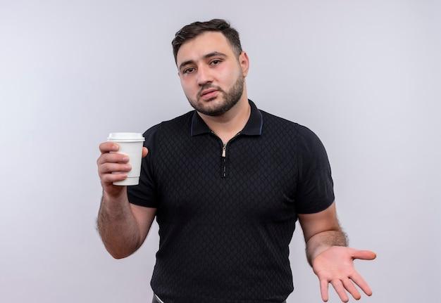 Jonge, bebaarde man in zwart shirt met koffiekopje op zoek verward