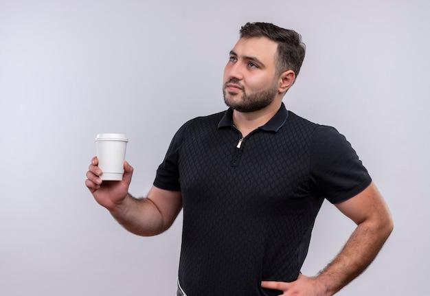 Jonge, bebaarde man in zwart shirt met koffiekopje opzij kijken met peinzende uitdrukking op gezicht