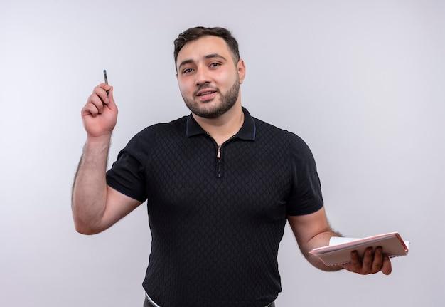 Jonge, bebaarde man in zwart shirt met notitieboekje en pen op zoek zelfverzekerd