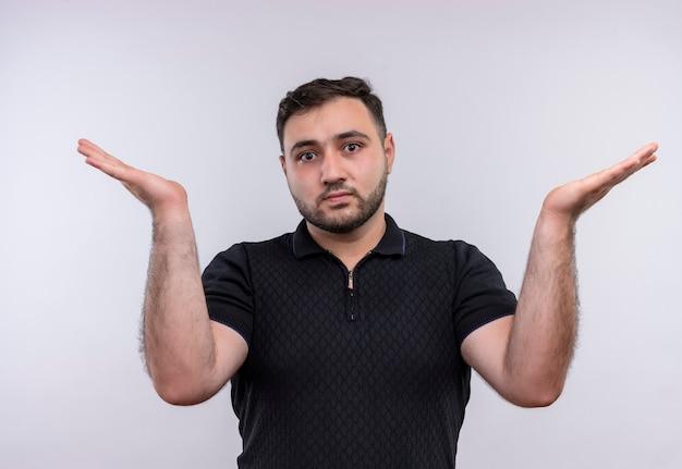 Jonge, bebaarde man in zwart shirt op zoek verward en uncerating schouders ophalen