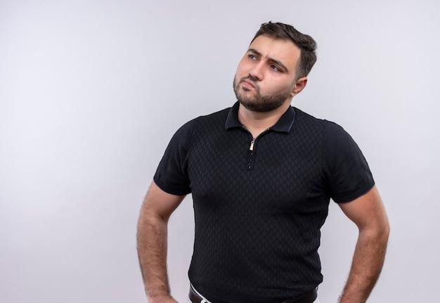Jonge, bebaarde man in zwart shirt opzij kijken met peinzende uitdrukking denken, twijfels hebben
