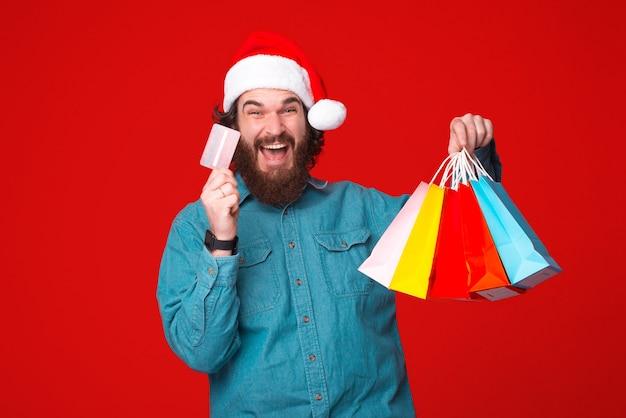 Jonge, bebaarde man is enthousiast over het betalen met een creditcard voor zijn aankopen.