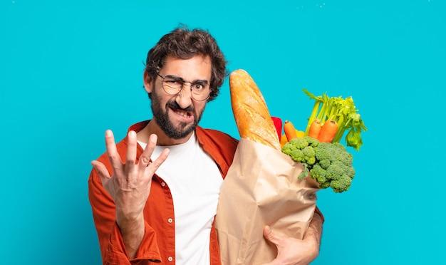 Jonge, bebaarde man kijkt boos, geïrriteerd en gefrustreerd, schreeuwt wtf of wat is er mis met je en houdt een zak met groenten vast