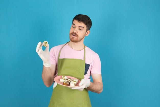 Jonge, bebaarde man kijkt naar zelfgemaakte cakebroodjes op een blauw.