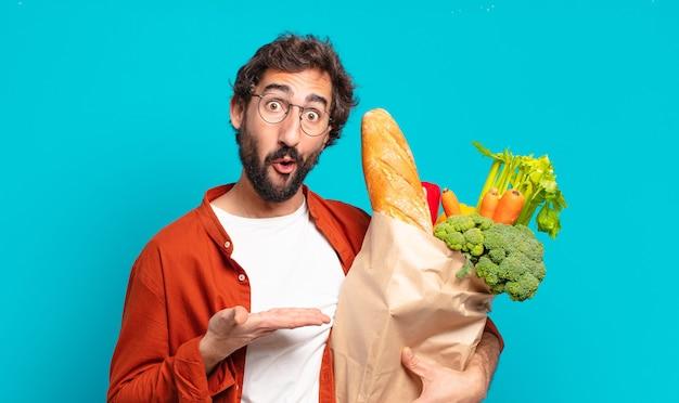 Jonge, bebaarde man kijkt verbaasd en geschokt, met open mond naar beneden terwijl hij een voorwerp vasthoudt met een open hand aan de zijkant en een zak met groenten vasthoudt