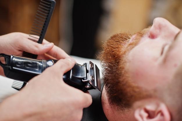 Jonge, bebaarde man krijgt kapsel door kapper zittend in een stoel bij herenkapper. kapper ziel.